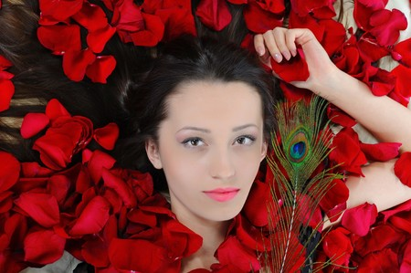 Portrait of beautiful brunette in red rose petals with a peacock feather photo
