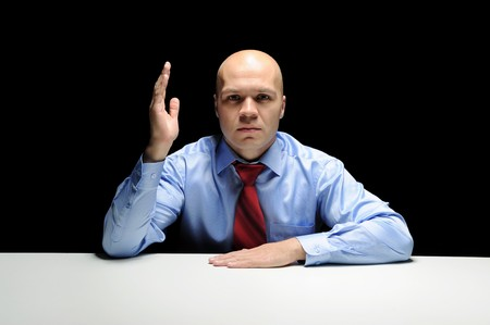 Portrait of young businessman holding hand up in a dark room photo