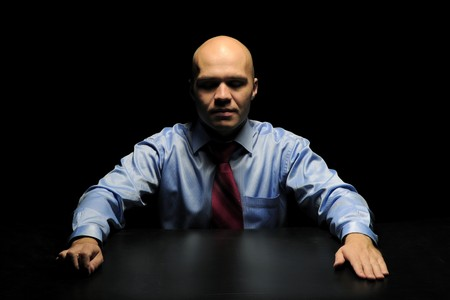 Portrait of young businessman in a dark room photo