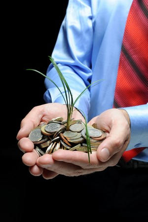 Image sprout germ grows out of coins in the hands of man Stock Photo - 7905843