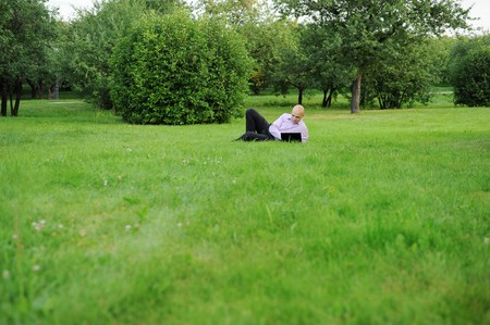 Businessman with laptop lying on green grass in the park photo