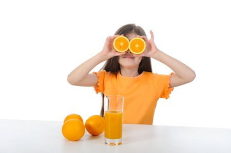 girl at the table with oranges and juice. Isolated on white background photo