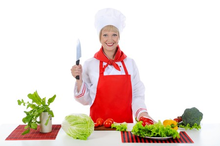 blond girl cuts the tomatoes in the kitchen. Isolated on white background photo