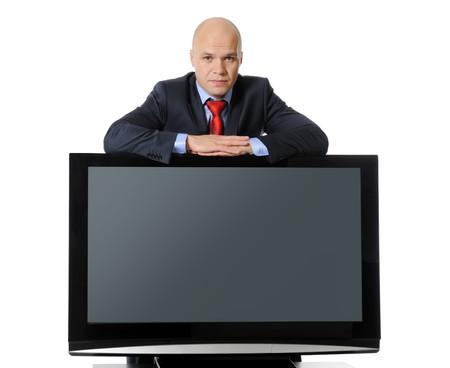 bedside: Joven exitoso hombre de negocios con un traje negro con una televisi�n de plasma de gran tama�o en la mesita. Aislados en fondo blanco