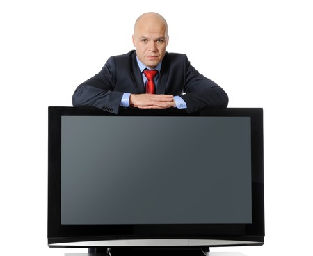 Young successful businessman in a black suit with a large plasma television on the bedside table. Isolated on white background photo
