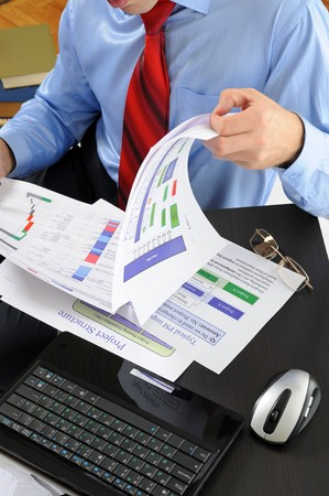 Image of a businessman working with documents in the office of the table photo