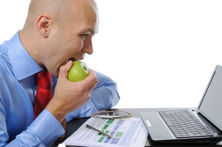 Image of a businessman in an office at the computer eating a green apple. Isolated on white background photo