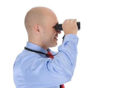 bald businessman looking  through binoculars. Isolated on white background photo