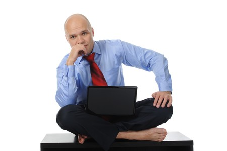 Businessman with a laptop sitting in the lotus position on the table. Isolated on white background photo