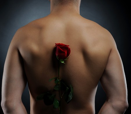 Picture a man  holding a red rose behind his back. Isolated on white background photo