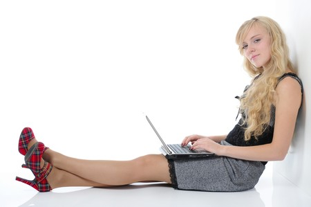 Blonde woman with laptop sitting on the floor near the wall. Isolated on white background Stock Photo - 7983513