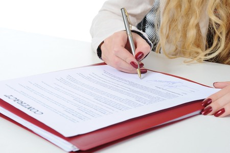 Businesswoman signs a contract. Isolated on white background photo