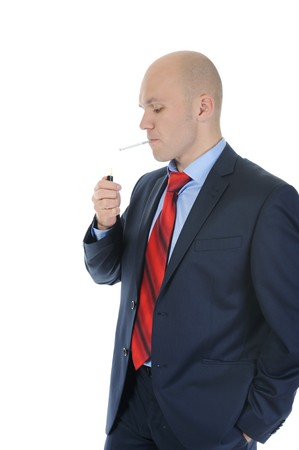 Businessman in suit lights a cigarette. Isolated on white background photo
