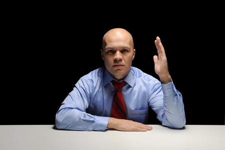 Portrait of young businessman holding hand up in a dark room Stock Photo - 7983494