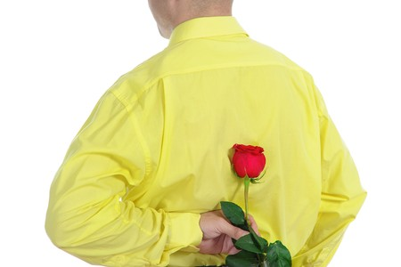Picture a man in a yellow shirt holding a red rose behind his back. Isolated on white background Stock Photo - 7983482