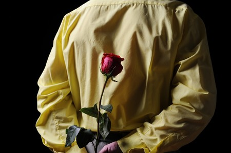 Picture a man in a yellow shirt holding a red rose behind his back. Stock Photo - 7983534