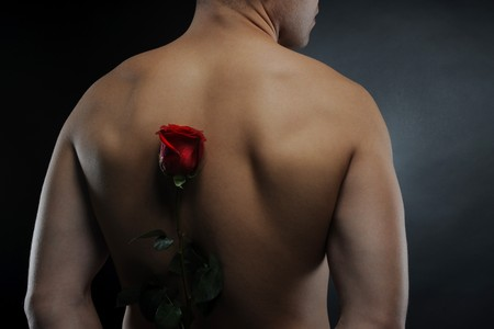 Picture a man  holding a red rose behind his back. Isolated on white background Stock Photo - 7983503