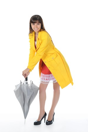 beautiful smiling girl in  in a yellow raincoat with umbrella.  Isolated on white background Stock Photo - 7983483