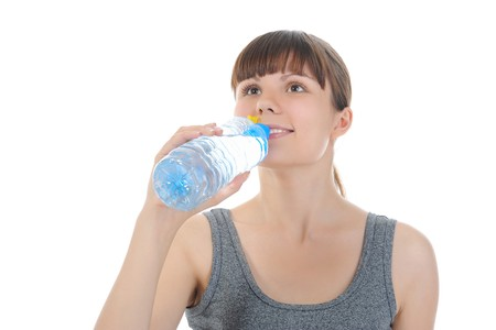 Athletic young woman drinking water from a bottle. Isolated on white background photo
