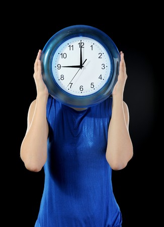 woman in a dark blue dress holds hours in the face of