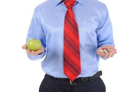 Apple and pills in the hands of a businessman. Isolated on white background Stock Photo - 7983577