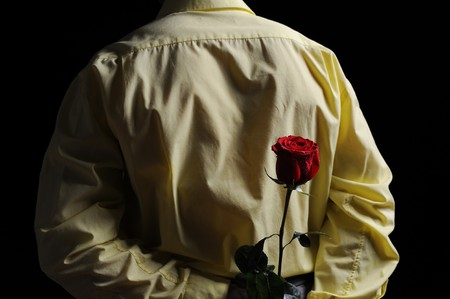 Picture a man in a yellow shirt holding a red rose behind his back. photo