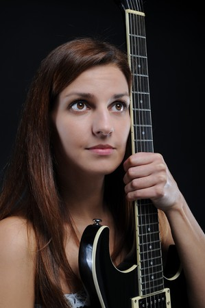 beautiful young woman with a black guitar in his hand. Isolated on white background photo