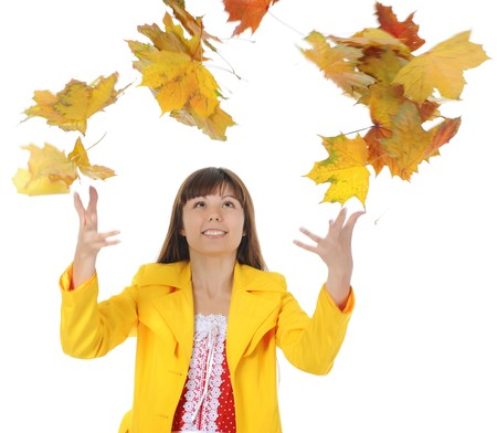 beautiful smiling girl in  in a yellow raincoat throws up maple leaves.  Isolated on white background photo