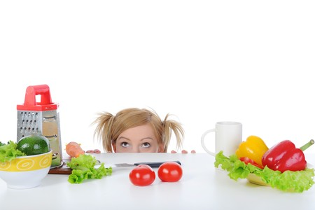 smiling blonde looks for fresh vegetables. Isolated on white background Stock Photo - 7983601