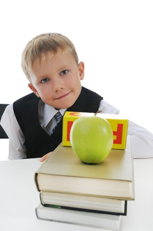 little boy at his desk with books and apple. Isolated on white background photo