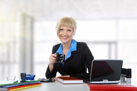 Young woman drinking coffee in the office.  photo