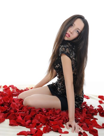 Portrait of young brunette in red rose petals. Isolated on white background photo