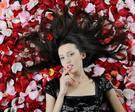 Portrait of beautiful brunette in red rose petals photo