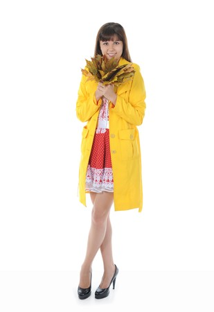 beautiful smiling girl in  in a yellow raincoat with maple leaves.  Isolated on white background photo