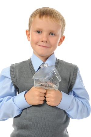 Funny little boy holding a toy house in the hands. Isolated on white background photo