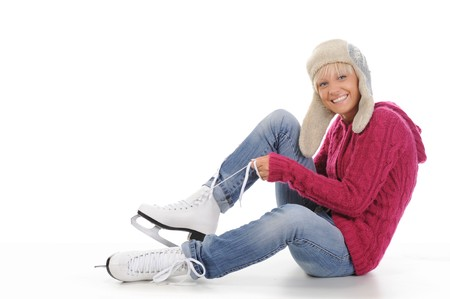 Beautiful girl in winter clothes puts on skates. Isolated on white background photo