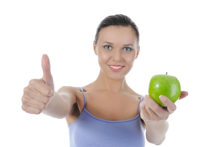 Athletic girl holding a green apple in hand. Isolated on white background photo