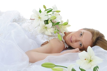 young bride with a bouquet of lilies lying on the floor in a bright room. Isolated on white background photo