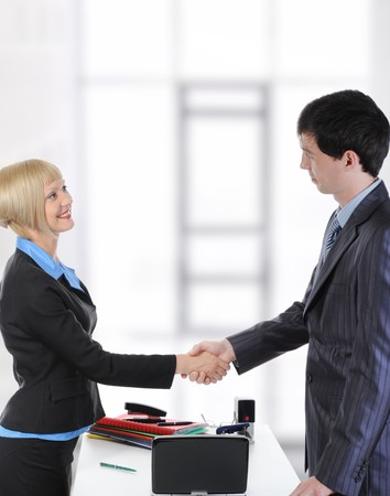 Handshake two business partners in a bright office. photo