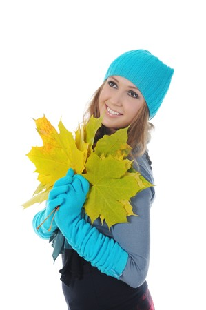 Smiling woman in winter style with a maple leaf in his hand. Isolated on white photo