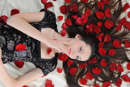 Portrait of beautiful brunette in red rose petals Stock Photo - 8062008