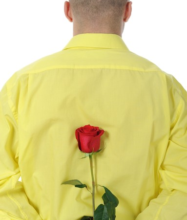 Picture a man in a yellow shirt holding a red rose behind his back. Isolated on white background Stock Photo - 8061978