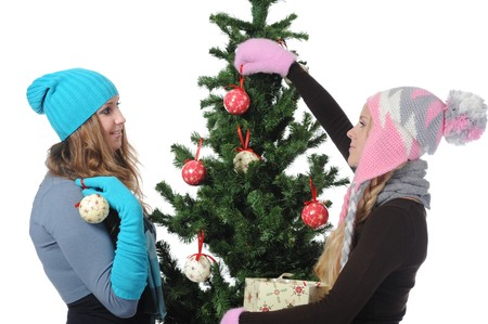 adorn: Image of two young women adorn the Christmas tree toys. Isolated on white background