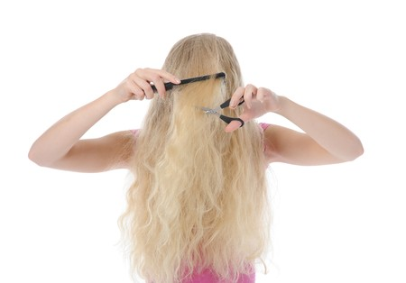 young girl with backcombing hair and scissors. Isolated on white background photo