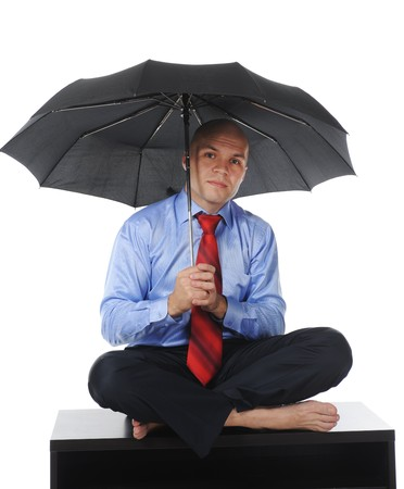 Image of a businessman sits on a table with an umbrella in his hand. Isolated on white background photo