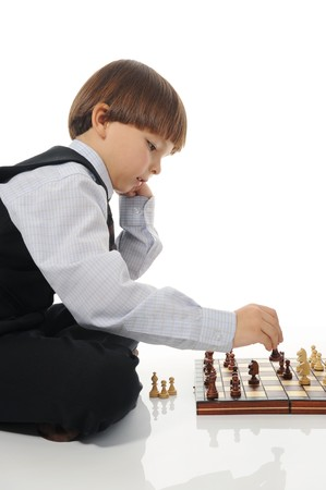 schoolboy playing chess. Isolated on white background photo