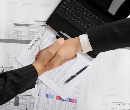 manos trabajo: Apret�n de manos de dos socios comerciales despu�s de firmar un contrato. Centrarse en los documentos  Foto de archivo