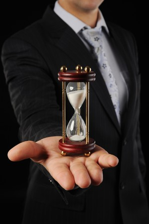 expertise concept: Businessman with hourglass in hand in a dark room
