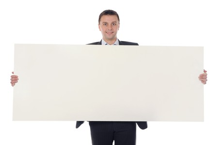 Young smiling businessman in black suit holding large blank. Isolated on white background photo