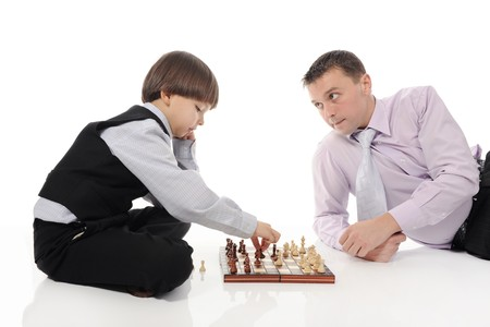 Dad and son playing chessin a bright room. Isolated on white background photo